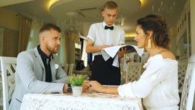 El camarero trajo la taza de café para los pares hermosos en un café metrajes