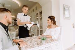 El camarero trajo la taza de café para los pares hermosos en un café Fotos de archivo libres de regalías