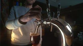 El camarero utiliza el golpecito de la cerveza y vierte la cerveza de barril al vidrio en cerveza oscura valiente a cámara lenta metrajes