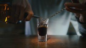 El camarero vierte el alcohol transparente al tiro acodado con el licor del dakr por la cuchara de la barra en alcohol a cámara l almacen de video
