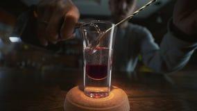El camarero vierte el alcohol transparente al tiro acodado con el licor rojo por la cuchara de la barra en alcohol a cámara lent almacen de video