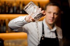 El camarero vierte el cóctel alcohólico con hielo usando el tamiz y glas Fotografía de archivo