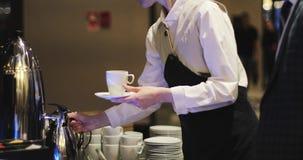El camarero vierte el café y la leche en la taza para el cliente o el cliente almacen de video