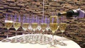 El camarero vierte el champán en copa, en un restaurante, el camarero vierte el champán en cristales, restaurante almacen de metraje de vídeo