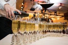 El camarero vierte el champán en los vidrios en el partido Imagen de archivo