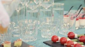 El camarero vierte el agua en un vidrio en un banquete almacen de video