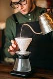 El camarero vierte el agua hervida caliente en un pote del café Fotografía de archivo libre de regalías