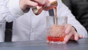 El camarero vierte el jugo en el vidrio con hielo en el contador de la barra, barkeeper prepara el cóctel de enfriamiento, cóctel almacen de metraje de vídeo
