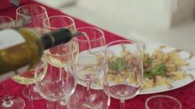 El camarero vierte el vino blanco en vidrios en un banquete almacen de metraje de vídeo