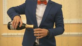 El camarero vierte el vino espumoso en el vidrio metrajes