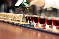 El camarero vierte la bebida alcohólica Imagen de archivo libre de regalías