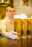 El camarero vierte la cerveza en un vidrio en la barra fotos de archivo libres de regalías