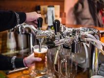 El camarero vierte la cerveza en un vidrio en una pequeña cerveza Imagenes de archivo