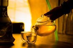 El camarero vierte té de una tetera en un restaurante Imagenes de archivo