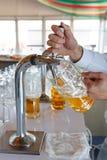 El camarero vierte una cerveza espumosa ligera en una taza grande durante el partido de Oktoberfest Fotos de archivo libres de regalías
