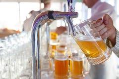 El camarero vierte una cerveza espumosa ligera en una taza grande durante el partido de Oktoberfest Imagenes de archivo