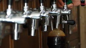 El camarero vierte una cerveza oscura en una botella plástica Cierra la tapa de la botella y pone en un bolso blanco almacen de video