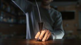 El camarero vierte el whisky al aparejo en la cámara lenta, haciendo de bebida del alcohol, el cóctel en la barra, camarero en el almacen de metraje de vídeo