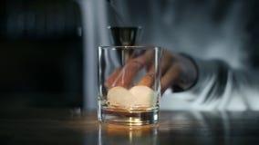 El camarero vierte el whisky al aparejo y entonces al vidrio con el hielo, haciendo de bebida del alcohol, cóctel en la barra almacen de video
