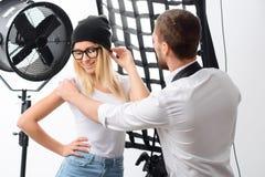 El cameraman ajusta postura del modelo joven Foto de archivo libre de regalías