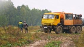 El camión con la carrocería cargada conduce a lo largo de paradas del camino en los trabajadores por el bosque almacen de metraje de vídeo