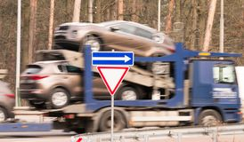 El camión de Blured es nuevos coches llevados en la plataforma Imagen de archivo libre de regalías