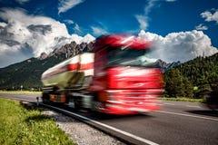 El camión de combustible acomete abajo de la carretera en el fondo las montañas T Foto de archivo libre de regalías