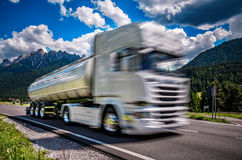 El camión de combustible acomete abajo de la carretera en el fondo las montañas T Imagen de archivo libre de regalías
