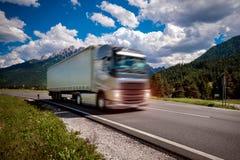 El camión de combustible acomete abajo de la carretera en el fondo las montañas T Fotos de archivo