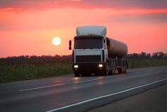El camión de combustible va en la carretera en puesta del sol Imágenes de archivo libres de regalías