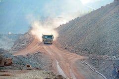 El camión de descargador que conduce en una mina activa de la mina del pórfido oscila Foto de archivo