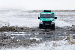 El camión de la reunión 4WD supera una charca mitad-congelada Imagenes de archivo