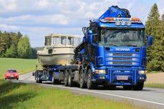 El camión de Scania 124 acarrea un barco Imagen de archivo libre de regalías