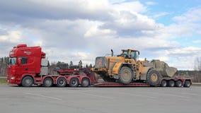 El camión de Scania 164G semi transporta el cargador de la rueda como carga de gran tamaño Foto de archivo libre de regalías