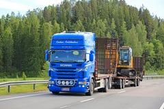 El camión de Scania V8 acarrea nueva Holland Crawler Excavator fotografía de archivo