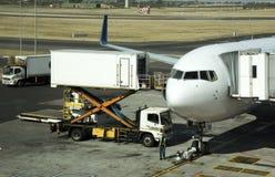 El camión del abastecimiento y scissor la elevación que suministra un avión de pasajeros Foto de archivo libre de regalías