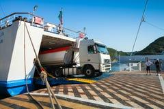 El camión del cargo deja hacia fuera el transbordador en puerto Foto de archivo