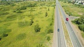 El camión rojo se mueve a lo largo de la carretera a la ciudad distante en horizonte metrajes