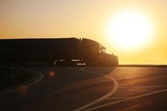 El camión va en la carretera en puesta del sol Imagenes de archivo