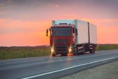 El camión va en la carretera en puesta del sol Imágenes de archivo libres de regalías