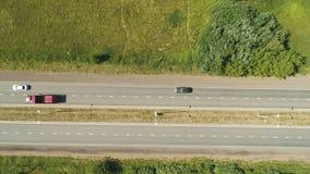 El camión vacío rojo conduce a lo largo del camino moderno más allá de la opinión de la parte superior de los campos almacen de video