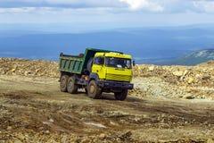 El camión volquete está conduciendo en un camino de la montaña Foto de archivo
