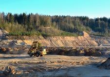 El cami?n volquete amarillo pesado descarga el suelo en un hoyo de arena de la mina a cielo abierto imágenes de archivo libres de regalías