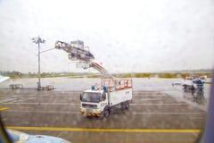 El camión de descongelación descongela un avión antes Imagenes de archivo