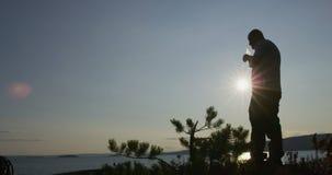 El caminante activo del hombre toma una rotura y un agua potable por el mar en la puesta del sol almacen de metraje de vídeo