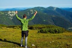 El caminante alegre, individuo joven se coloca con los brazos abiertos en las montañas Fotografía de archivo
