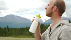 El caminante bebe el agua clara encima de las montañas almacen de metraje de vídeo