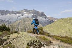El caminante camina con un paisaje alpino impresionante en las montañas Imagen de archivo libre de regalías