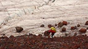 El caminante cansado con la mochila pesada grande se traslada desde el glaciar a la moraine el hombre va a lo largo de un rastro  almacen de metraje de vídeo