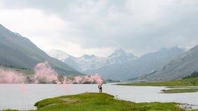 El caminante con la mochila que camina encima de una montaña con el sol señala por medio de luces Forma de vida activa sana de la almacen de metraje de vídeo